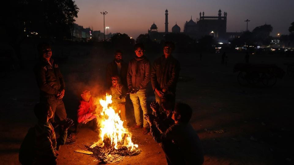 Farmaan (4th L), and other homeless and daily wage labourers keep themselves warm around a bonfire. More than 20 years ago, Ruby Khan and her husband, Nisar, came to New Delhi, hoping to find work and some sort of future in the capital. They were desperately poor and barely educated. (Altaf Qadri / AP)