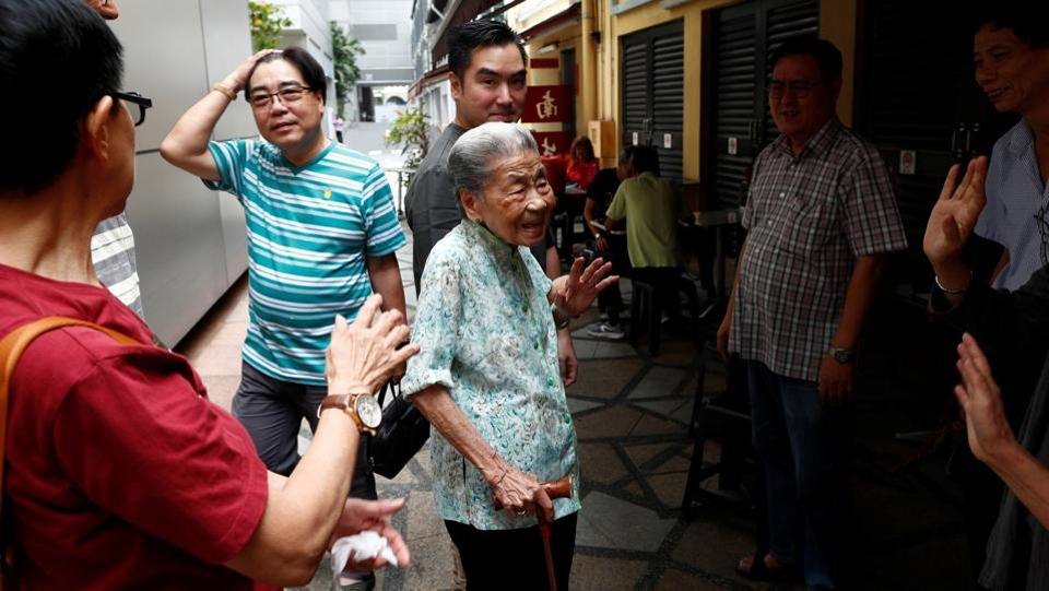 "Leong Yuet Meng of Nam Seng Noodle House is greeted by longtime patrons and family friends outside her shop. ""I don't think hawker centres will exist in the next 50 years,"" Lee said. ""It's too much hard work, we have to put in 16 hours a day sometimes. It's hot. Kids nowadays wouldn't want to work here."" (Edgar Su / REUTERS)"