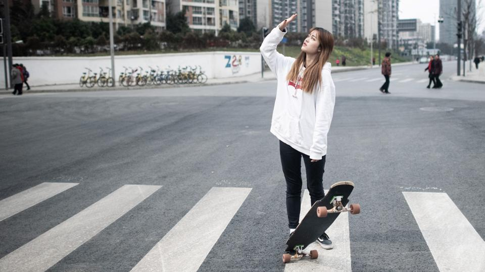 Longboarder Mu Qing poses with her board in Chengdu. 21-year-old Mu is among a new generation of female longboarders in China. With over half a million followers on social media, she is one of longboarding's biggest stars in the country. (Fred Dufour / AFP)