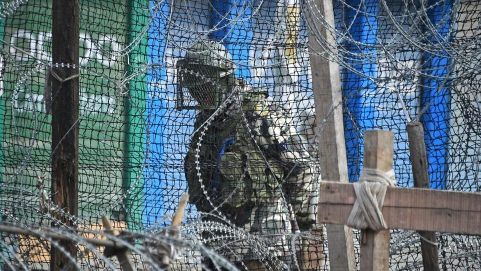 A paramilitary trooper stands guard behind a barbed fence wire outside a bunker during a one-day strike called by Kashmiri traders against the Jamaat-e-Islami ban, in Srinagar, Jammu and Kashmir. (Tauseef Mustafa / AFP)