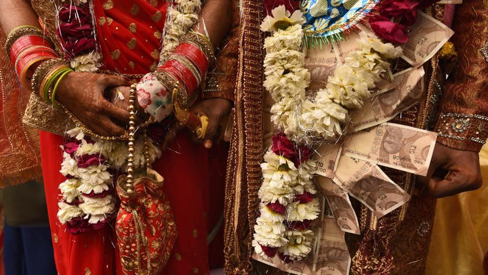 A groom and bride stand after performing rituals during a mass wedding for eight couples at Hanuman Vatika Ramleela Maidan, in New Delhi. (Burhaan Kinu / HT Photo)