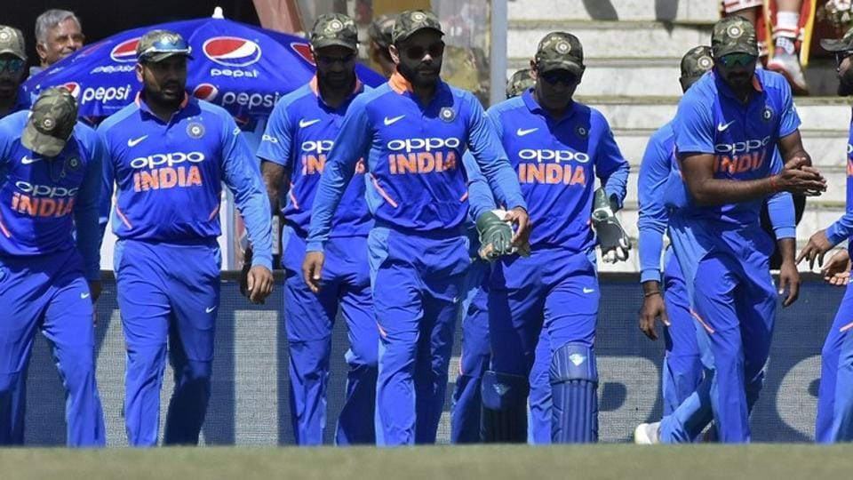Cricket - India v Australia - Third One-Day International - Jharkhand State Cricket Association Stadium, Ranchi, India - March 8, 2019 - India's captain Virat Kohli (C) and his teammates wearing army camouflage-style caps walk onto the field. REUTERS/Stringer