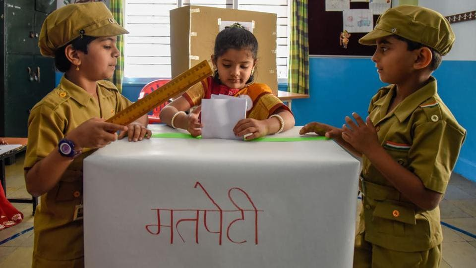 Mock police officers of Abhinav pre primary school keep vigil while a civilian casts her vote. (Sanket Wankhade/HT PHOTO)
