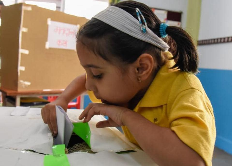 A student is seen casting her vote,  in the mock elections of Abhinav pre primary school. (Sanket Wankhade/HT PHOTO)