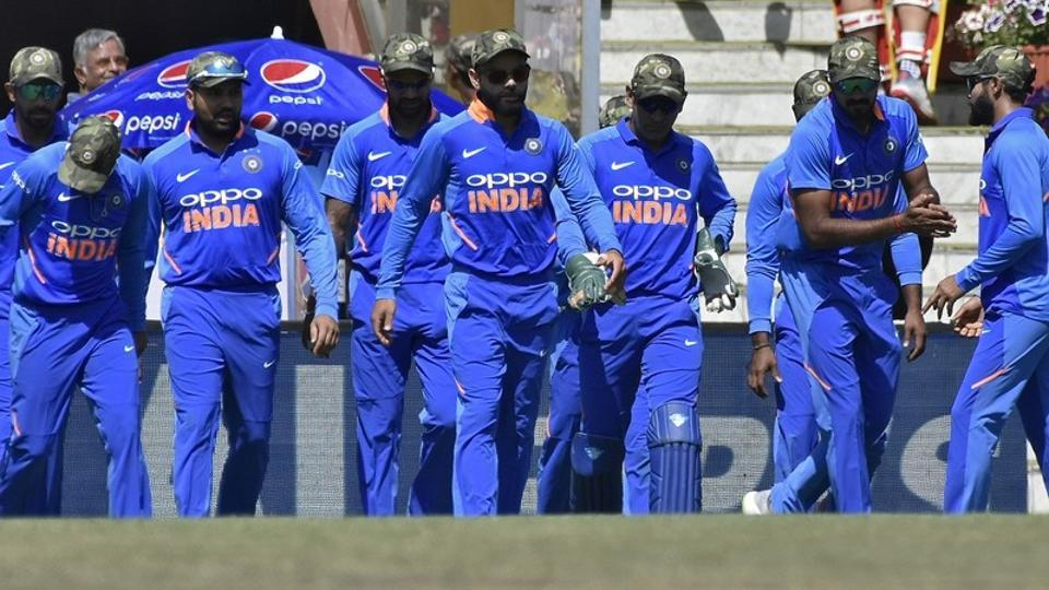 Virat Kohli (C) and his teammates wearing army camouflage-style caps walk onto the field.