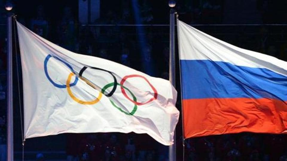 Olympic and Russian flags being hoisted during the Opening Ceremony of the Sochi Winter Olympics.