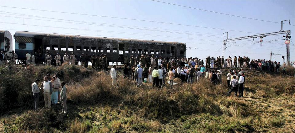 People gather near the bogies of Samjhuata Express after an explosion.