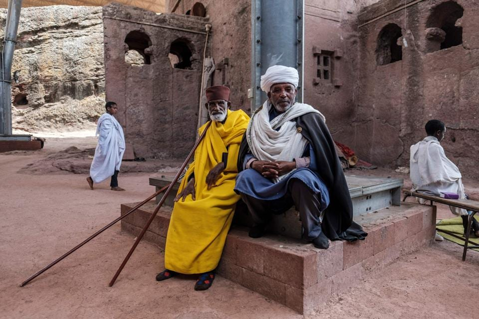 An Ethiopian Orthodox priest Mekonnen Fatne (R) near the church of Saint Mary which is covered by a shelter to protect its rock-hewn structure from erosion in Lalibela, Ethiopia. Standing among his Ethiopian Orthodox faithful, Fatne looked upon the nine-centuries-old church they feared could be wrecked at any minute. (Eduardo Soteras / AFP)