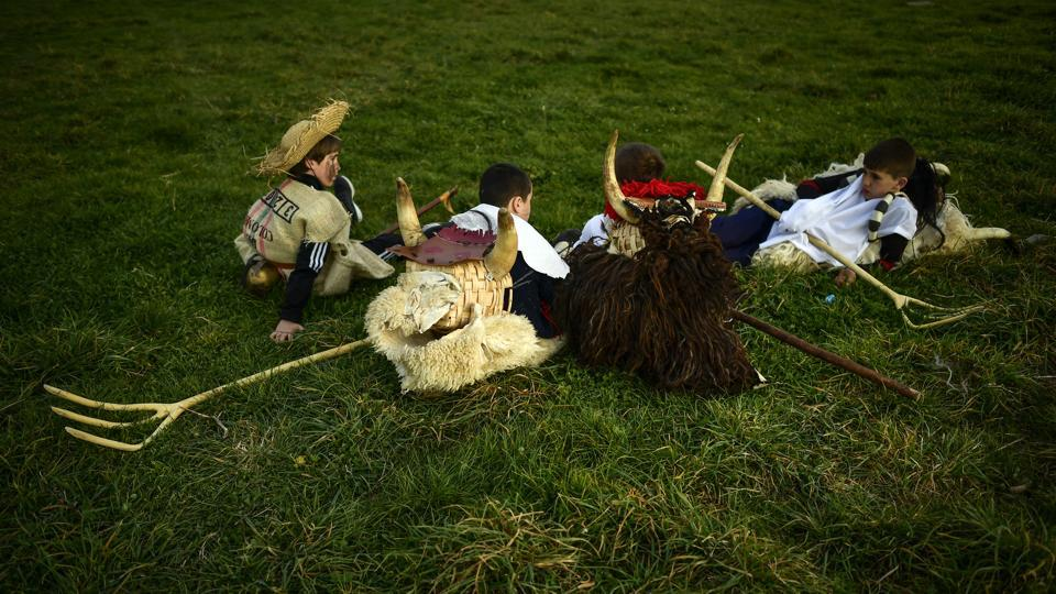 Young momotxorros rest on the ground before taking part in a carnival. Called so in the Basque language, these half-human and half-animal creatures display the skin of sheep on their backs and white long pieces of sheets stained with bright-red animal blood on the front. (Alvaro Barrientos / AP)