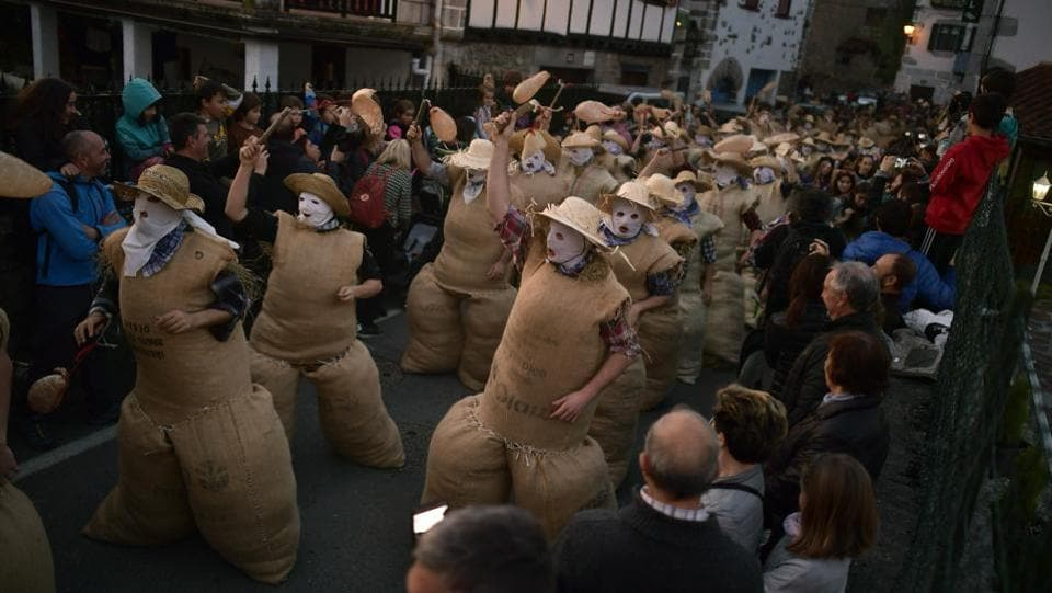 After sunset, covering their faces with white handkerchiefs, stuffed into sacks full of straw, and holding a stick with an inflated animal's bladder used to hit people, the Zaku Zaharrak characters parade for hours through the village dancing and singing while a band plays music. (Alvaro Barrientos / AP)