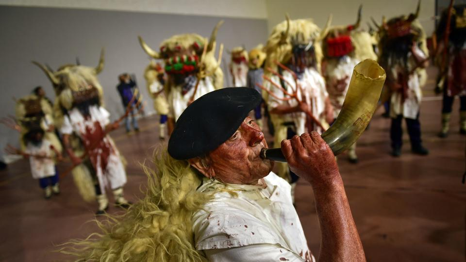 A man plays a horn as momotxorros take part in a carnival. The heads are topped with the horns of a bull over a basket normally used for agricultural produce, and horsehair covers the faces of anonymous revelers taking part in the riotous celebration. (Alvaro Barrientos / AP)