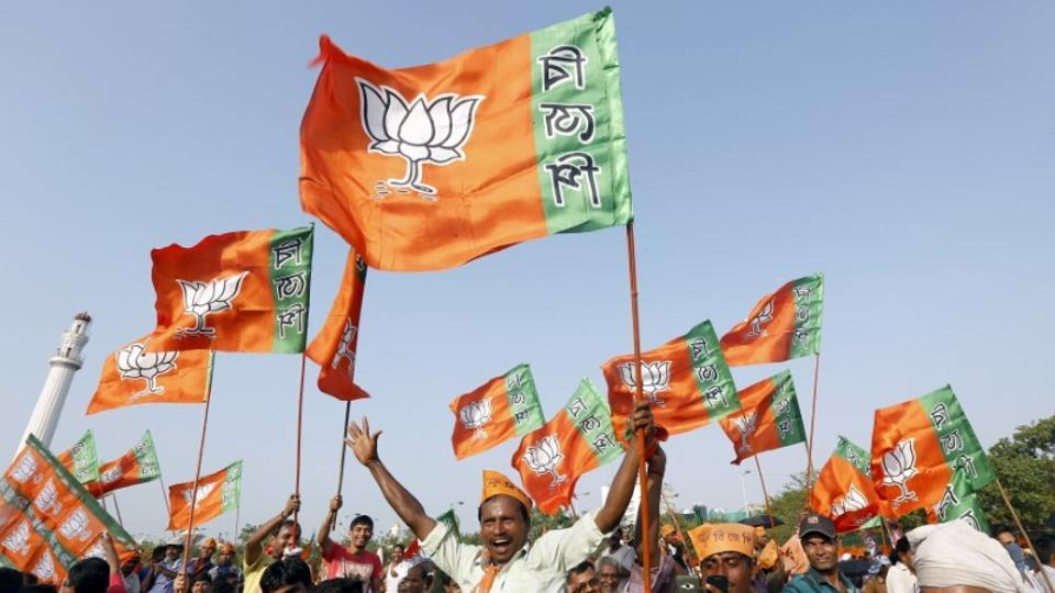 Supporters of India's ruling Bharatiya Janata Party (BJP) wave their party's flags at an election campaign rally in Kolkata.