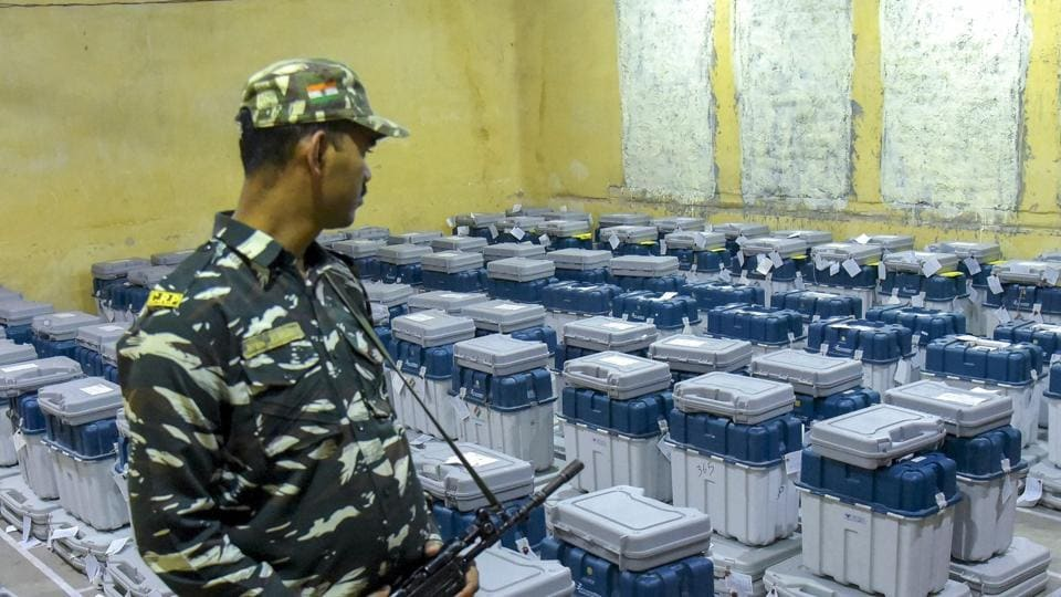 A para-military jawan guards stands guard at a facility where EVMs have been stored.