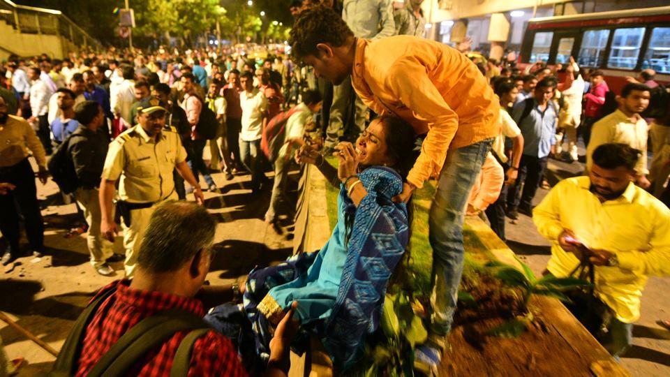 An injured woman is helped at the site of a collapsed footbridge outside the Chhatrapati Shivaji Terminus railway station in Mumbai on Thursday.