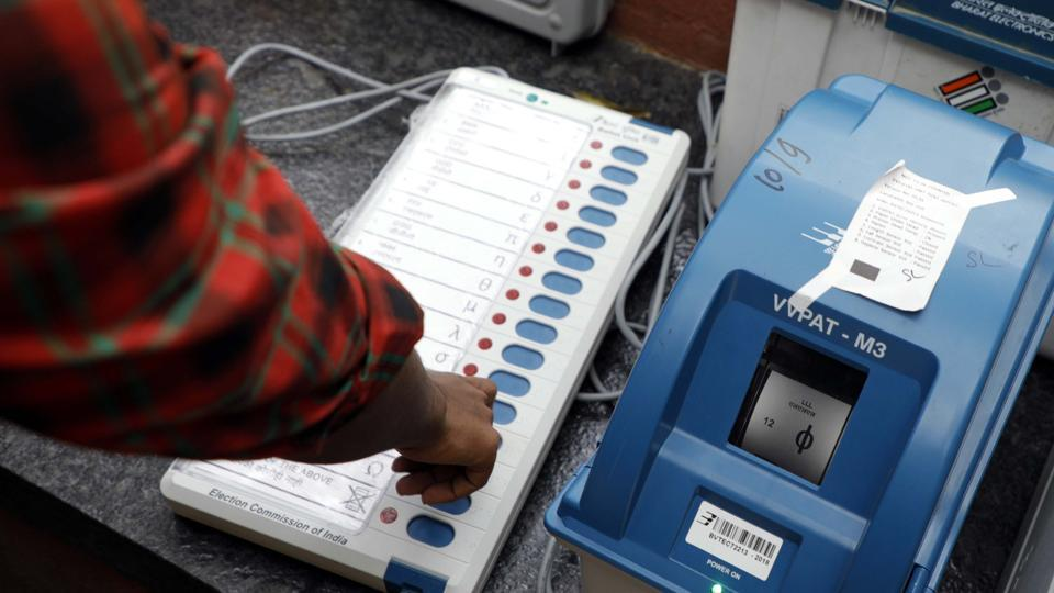 An election commission official gives a demonstration of how to use an EVM