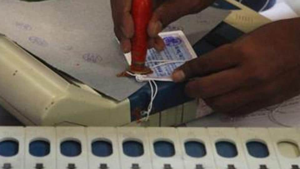 An Election Commission official seals an EVM after an election.