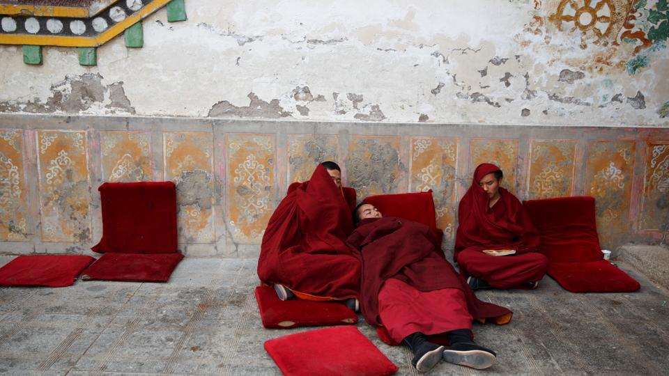 Buddhist monks rest outside a prayer hall between chanting sessions at Rongwo Monastery in the largely ethnic Tibetan town of Rebkong, Qinghai province, China. (Thomas Peter / REUTERS)