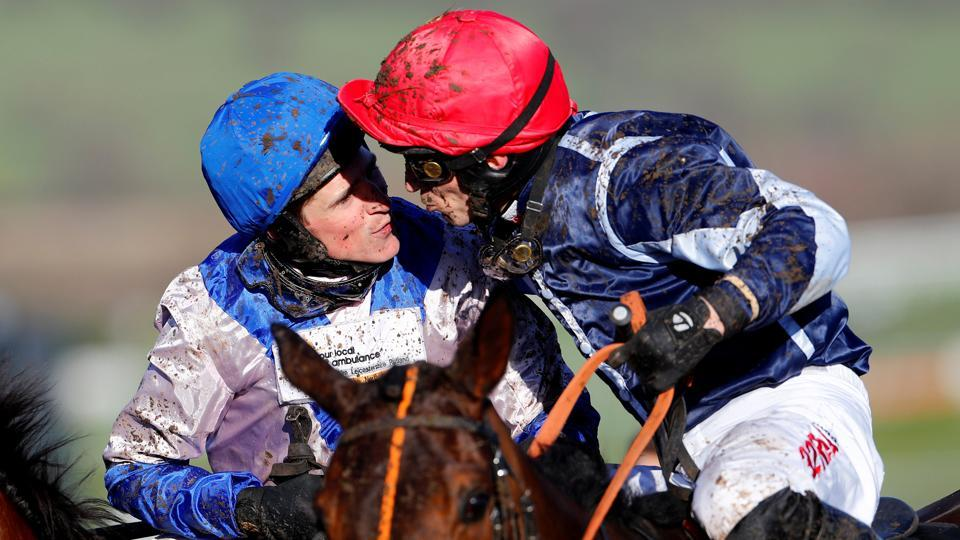 Harry Skelton on Roksana kisses P J Brennan on Cap Soleil after winning the 4:10 OLBG Mares' Hurdle (Grade 1) (Registered As The David Nicholson Mares' Hurdle) during the Cheltenham Festival at Cheltenham Racecourse, in England. (Eddie Keogh / REUTERS)