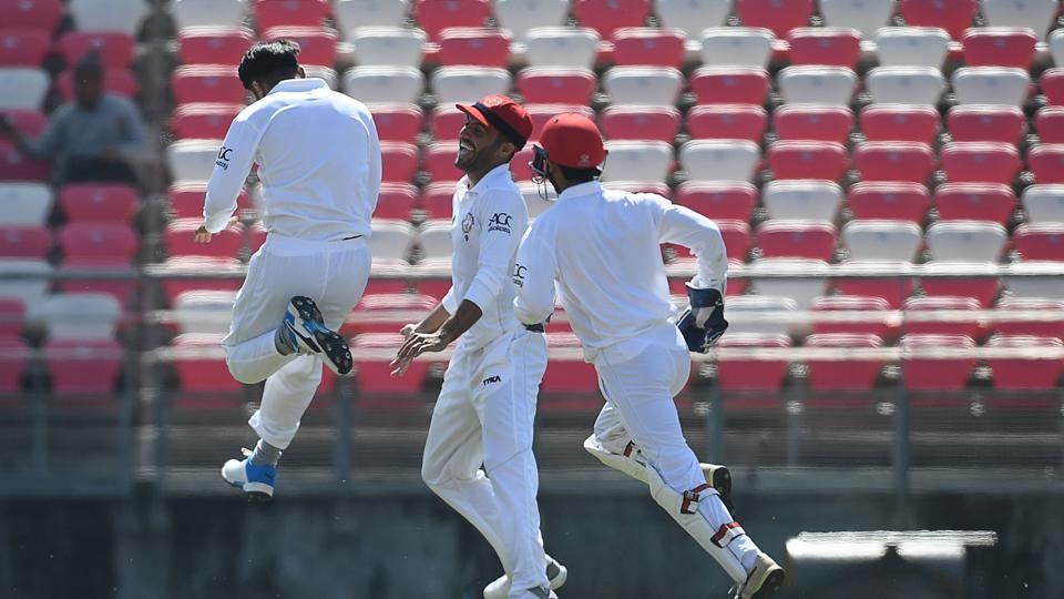 Afghanistan's Rashid Khan (L) celebrates the wicket of Ireland's Stuart Poynter during the day one of the test match between Afghanistan and Ireland