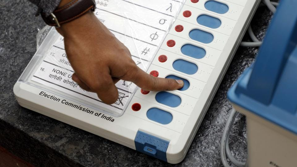 An election commission official gives a demonstration of how to use an EVM.