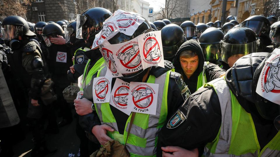"Police officers with stickers put by activists of Ukrainian nationalist parties block a street during a rally to demand an investigation into the corruption of Ukraine's armed forces officials, in Kiev, Ukraine. The stickers read ""Poroshenko's Svinarchuks behind bars."" (Gleb Garanich / REUTERS)"