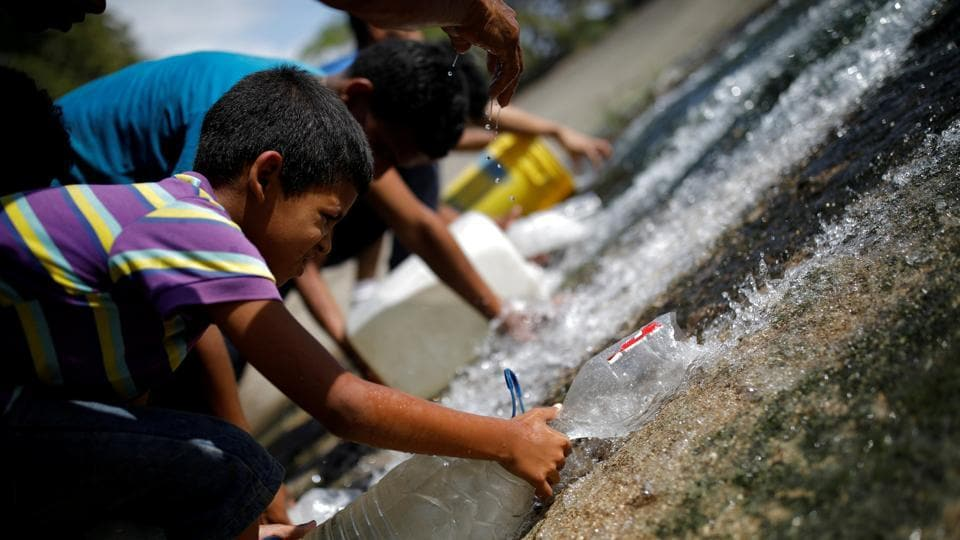 People collect water released through a sewage drain that feeds into the Guaire River, which carries most of the city's wastewater, in Caracas, Venezuela. (Carlos Garcia Rawlins / REUTERS)