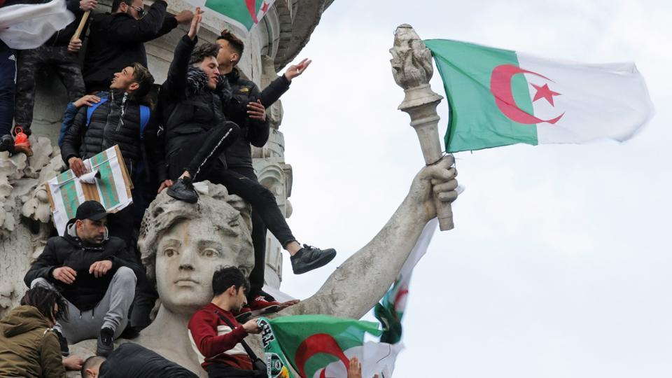 Protestors hold Algerian flags as they attend a demonstration against Algerian President Abdelaziz Bouteflika on the Place de la Republique, in Paris, France. Bouteflika finally relented and resolved to not run for a fifth consecutive term. (Philippe Wojazer / REUTERS)