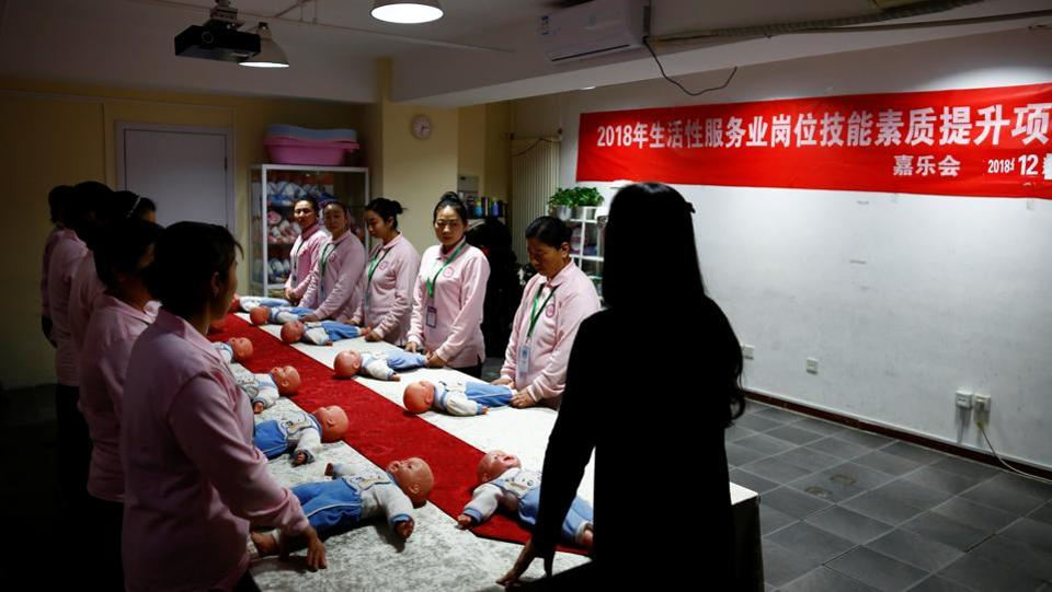 Students at Ayi University, a training program for domestic helpers, practice on baby dolls during a course teaching childcare in Beijing, China. (Thomas Peter / REUTERS)