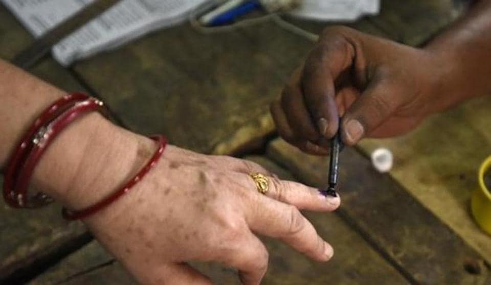 An Election Commission official inks a person after she cast her vote