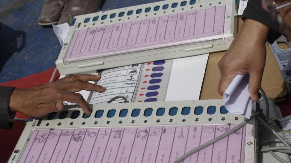 Polling officers check electronic voting machines at an EVM distribution centre.