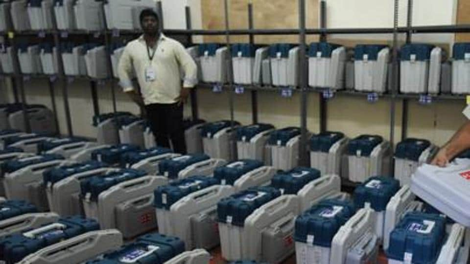 Polling staff check Electronic Voting Machines inside a strong room.