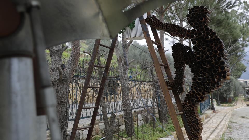 A sculpture depicts a man made out of artillery casings climbing a ladder. Nassar was forced to flee Lebanon during the civil war, and his grandmother was killed in the violence. But she and other characters of the artist's past live on, displayed in the nooks and crannies of his garden in the village of Remhala. (Joseph Eid / AFP)