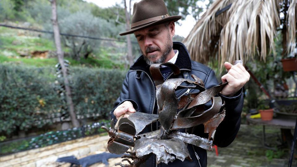 "Lebanese Artist Charles Nassar inspects his sculptures in the village of Remhala. Artist Charles Nassar has been transforming their dark, wrangled remains into sculptures to celebrate tradition and memory. ""I hate shrapnel, but I also love it at the same time,"" said the 54-year-old with a neat salt-and-pepper beard, in a garden south of Beirut. (Joseph Eid / AFP)"