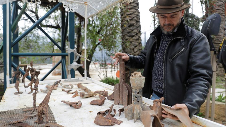 "Charles Nassar inspects his sculptures and collected pieces of shrapnel for his projects. ""The shrapnel takes on shapes in my mind... They guide me to what I should do with them,"" said the artist. Nassar first created his metal sculptures in Beirut, but after the war he decided to display them on land he owned in Remhala. (Joseph Eid / AFP)"