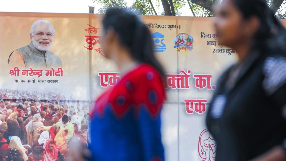 Pilgrims walk past an advertising banner featuring an image of  Prime Minister Narendra Modi during the Kumbh Mela in Prayagraj, Uttar Pradesh on January 16.