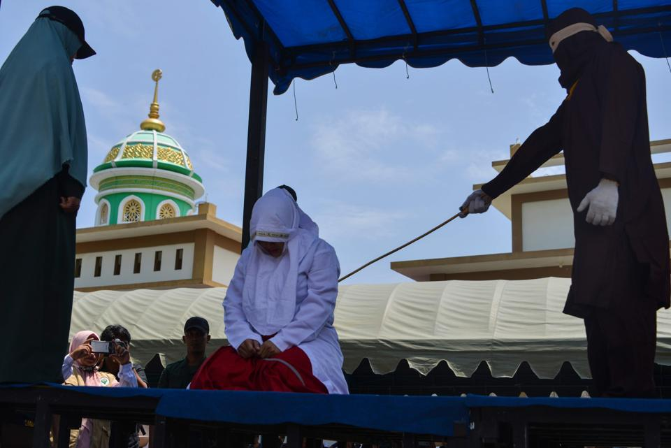 An Indonesian woman is whipped by a member of the Sharia police in public in Banda Aceh on March 20.