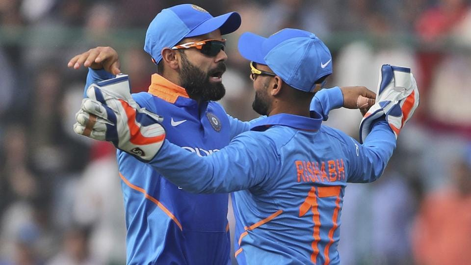 Virat Kohli, left, celebrates the dismissal of Australia's Peter Handscomb with teammate Rishabh Pant.