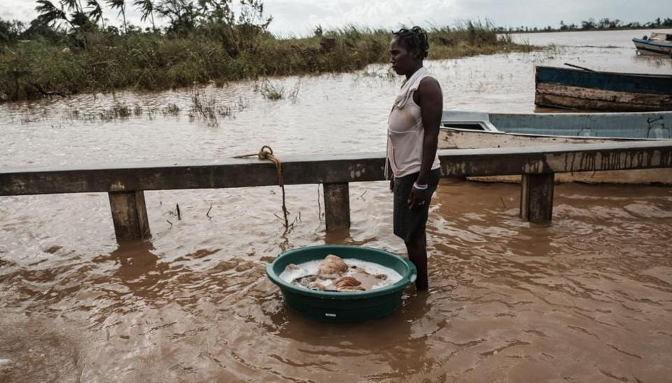 A woman washes a blanket in muddy waters at a boat landing place in Buzi, Mozambique, on March 23, 2019. - The death toll in Mozambique on March 23, 2019 climbed to 417 after a cyclone pummelled swathes of the southern African country, flooding thousands of square kilometres, as the UN stepped up calls for more help for survivors.