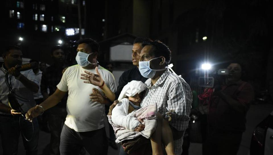 People rescue a patient after fire broke out at the Trauma Centre in AIIMS, New Delhi on March 24, 2019.