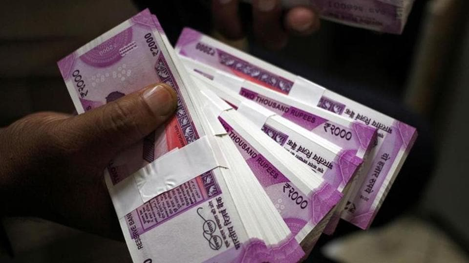 A cashier displays the new 2000 rupee banknotes inside a bank.