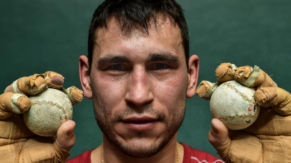 """Diego Iturriaga, 27, a player of Basque Ball known as """"pelotari"""", holds Basque Balls as he poses at Labrit court or fronton, in Pamplona, northern Spain. With their hands protected by layers of tightly-bound tape, the players take turns swatting a small, hard ball at speeds that reach 115 kilometers per hour. (Alvaro Barrientos / AP)"""