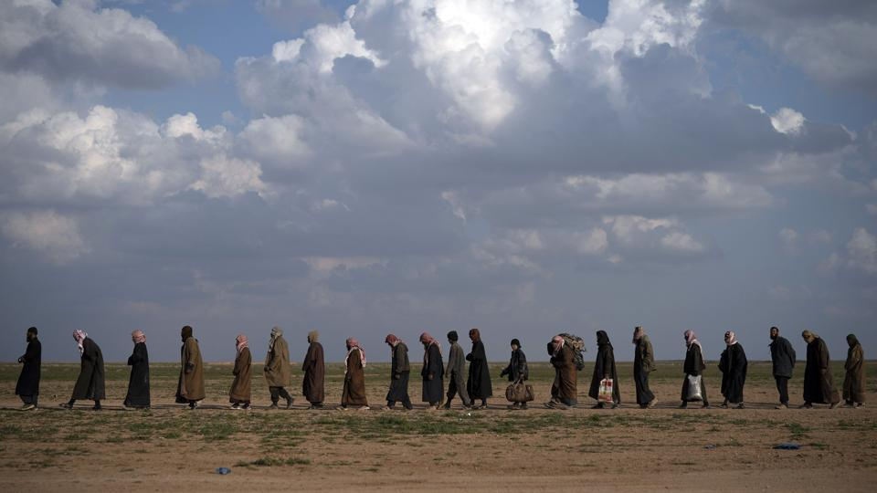 Men walk to be screened after being evacuated out of Baghouz. IS originated as an Al-Qaeda faction in Iraq, but took advantage of Syria's civil war to seize land there and declare a split. Oil production, extortion and stolen antiquities financed its agenda, which included slaughtering some minorities, slave auctions of captured women, grotesque punishments for minor crimes, and choreographed killing of hostages. (Felipe Dana / AP)