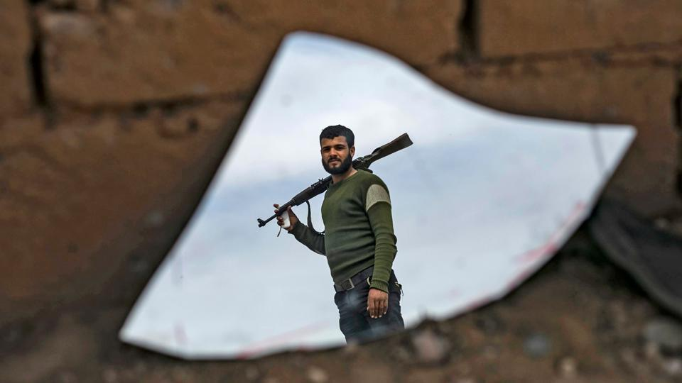 The image of fighter with the SDF is reflected on a broken mirror in the town of Baghouz. Some IS fighters still hold out in Syria's remote central desert, and in Iraqi cities they have slipped into the shadows, staging shootings or kidnappings. The United States believes the group's leader, Abu Bakr al-Baghdadi, is in Iraq. (Delil Souleiman / AFP)