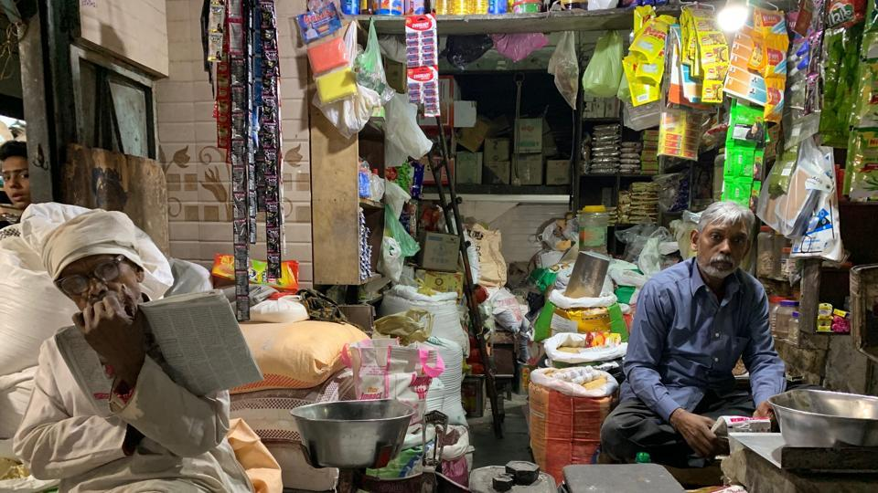 Babu Ram is spotted in this posture just about every evening poring over a newspaper while his son bustles about serving customers in the Central Delhi market.