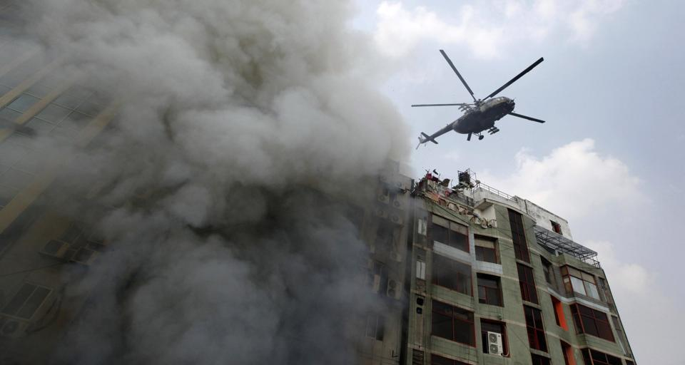A chopper hovers to evacuate people stuck in a multi-storied office building that caught fire in Dhaka on March 28