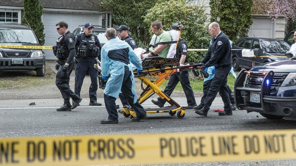 Paramedics and police officers remove a man from where two vehicles collided on Sand Point Way Northeast in Seattle on March 27.