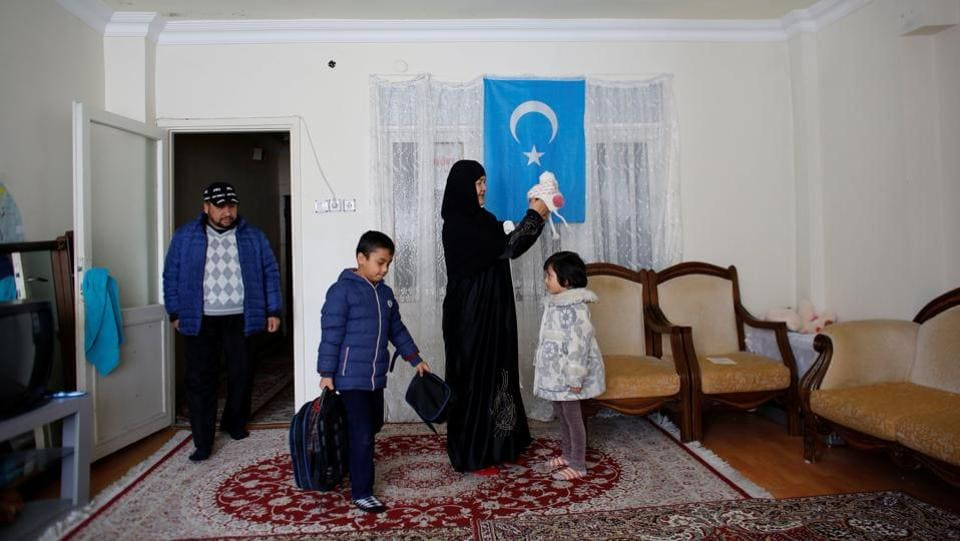 Qurbanjan Nourmuhammed and his wife Gulgine Mahmut get their children ready for school at their home in Istanbul. Nourmuhammed, his wife and five children came to Turkey in 2015, facing increased pressure from China to abandon Islamic practices such as wearing a headscarf, growing a beard and closing their restaurant for the Muslim holy month of Ramadan. (Murad Sezer / REUTERS)
