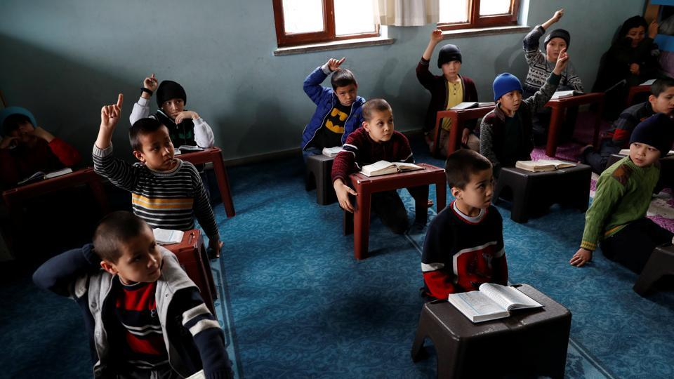 "Uighur boys who have lost at least one parent, raise their hands during a Koran class in a madrasa. ""Not all of the people whose passports have been labelled as risky... are problematic people,"" Tumturk said. ""People who can't retrieve a required document from China can experience the same issue."" (Murad Sezer / REUTERS)"