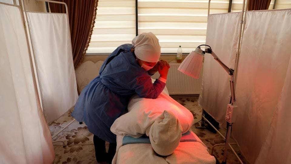 "Gulgine Idris, an Uighur reflexologist, treats a patient at a health centre in Istanbul, Turkey. Cengiz said many Uighurs had begun to fear they may be sent back to China. ""Turkey was seen as the only country that could stand up to China. In the past year, they have been fearing for their existence in Turkey,"" he said. (Murad Sezer / REUTERS)"