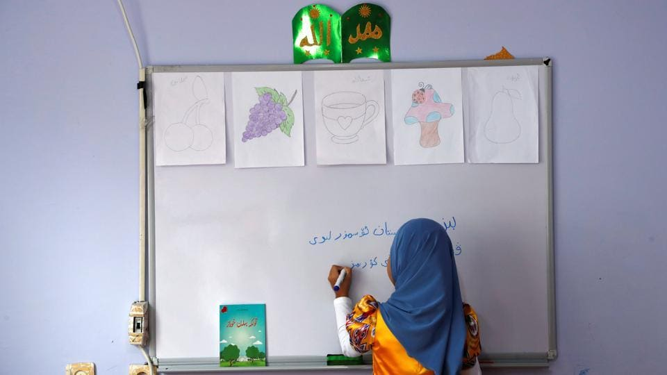 A girl writes, 'We, children of Turkestan, love our homeland' in the Uighur language in a classroom at a kindergarten. However, some hope has returned after Turkey took a harder stance against China at a UN Human Rights Council meeting last month, where Foreign Minister Mevlut Cavusoglu criticised Beijing for the alleged mistreatment of Uighurs and called for authorities to protect freedom of religion. (Murad Sezer / REUTERS)